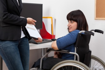 Woman on wheelchair analyzing charts with her boss