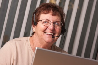 Smiling Senior Adult Woman with Telephone Headset In Front of Computer Monitor.